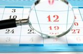 Magnifying glass and a calendar — Stock Photo