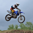 A leap over the hill motocross racer — Stock Photo