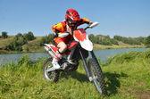 девушка сидящая на спортивном мотоцикле, среди озер и лесов. — Стоковое фото