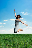 Young woman jumping at the field at sunny day — Stock Photo