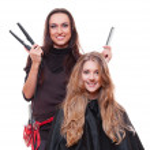 Studio shot of smiley hairdresser with straighteners — Stock Photo