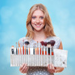 Woman with brushes for make-up over blue background — Stock Photo