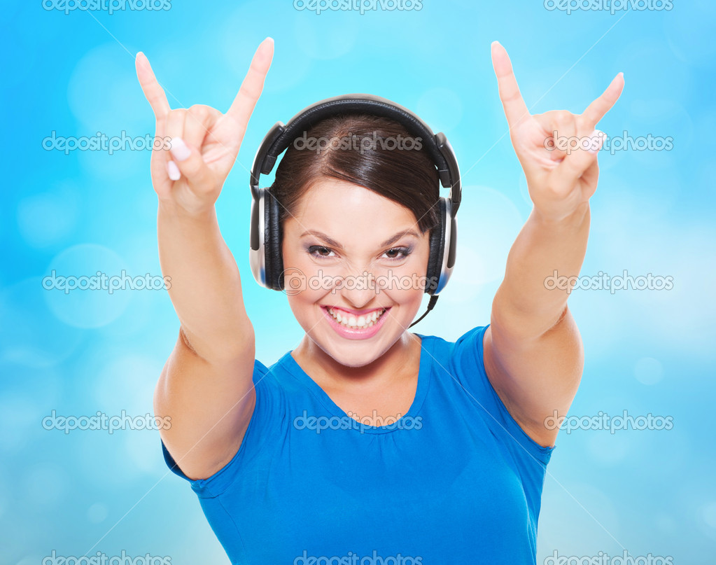 Cheerful young woman in headphones giving the rock and roll sign — Stock Photo #11343012