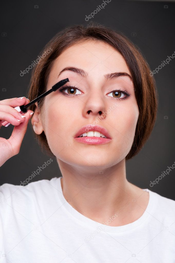 Young beautiful woman applying make up and looking at camera like in mirror — Stock Photo #11656776