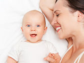 Baby and mother lying in bed — Stock Photo