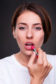 Woman painting her lips — Stock Photo