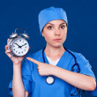 Serious doctor pointing at alarm clock — Stock Photo #12325767