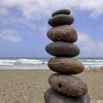 Balancing pebble stones on beach — Stock Photo