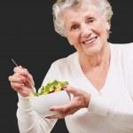 Portrait de femme senior manger salade sur fond noir — Photo