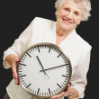 Portrait of a happy senior woman holding clock over black — Stock Photo #10776886