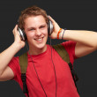 Portrait of cheerful young student listening music with headphon — 图库照片 #10777040