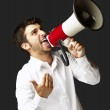 Portrait of young man shouting with megaphone over black backgro — Stock Photo