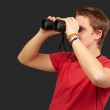 Portrait of young man looking through a binoculars over black ba — Stock Photo #10777283
