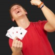 Portrait of young man doing a winner gesture playing poker over — Stock Photo #10777289