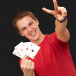 Portrait of young man doing a victory gesture playing poker over — Stock Photo #10777294