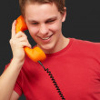 Portrait of young man talking on vintage telephone over black ba — Stock Photo #10777298