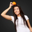Portrait of young woman holding orange on her head over black — Stock Photo #10777427