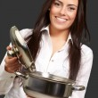 Portrait of young girl opening sauce pan over black background — Stock Photo #10777582