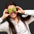 Portrait of young girl holding kiwi slices in front of her eyes — Stock Photo