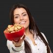 Portrait of young woman offering cereals bowl over black backgro — Stock Photo #10777618