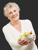 Portrait of senior woman showing a fresh salad over black backgr — Stock Photo