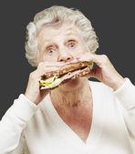 Starší žena jíst zdravé sendvič proti černé poza — Stock fotografie