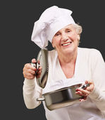 Portrait of cook senior woman opening sauce pan over black — Stock Photo