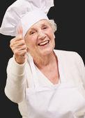 Retrato de mujer senior cocinero haciendo gesto de aprobación sobre negro — Foto de Stock