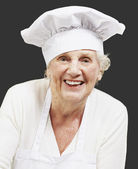 Senior woman cook holding a bowl with salad against a black back — Stock Photo