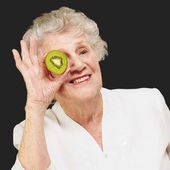 Portrait of senior woman holding kiwi in front of her eye over b — Stock Photo