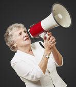 Portrait of senior woman holding megaphone over black background — Stock Photo