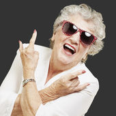 Portrait of senior woman doing rock symbol over black background — Stock Photo