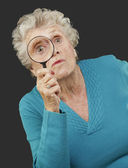 Portrait of senior woman looking through a magnifying glass over — Stock Photo