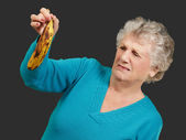 Senior woman holding a rotten banana over black background — Stock Photo