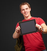 Portrait of young man holding a digital tablet over black backgr — Stock Photo