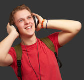 Portrait of cheerful young student listening music with headphon — Stock Photo