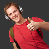 Portrait of cheerful young student listening music and gesturing — Stock Photo