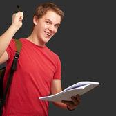 Portret przystojny student gospodarstwa notatnik i długopis na czarno — Zdjęcie stockowe