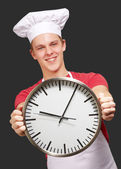 Portrait of young cook man holding clock over black background — Stock Photo