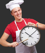 Portrait of young cook man pointing a clock over black backgroun — Stock Photo