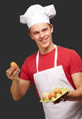 Portrait of young cook man holding egg box over black background — Stock Photo