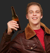 Portrait of young man holding beer on black background — Stock Photo