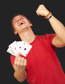 Portrait of young man doing a winner gesture playing poker over — Stock Photo