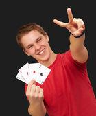 Portret młodego człowieka robi gest zwycięstwa, grając w pokera w ciągu — Zdjęcie stockowe