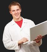 Portrét mladého studenta držení notebooku na černém pozadí — Stock fotografie