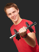 Portrait of young man with weights over black background — Stock Photo