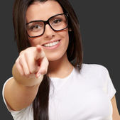 Portrait of young woman pointing with finger against a black bac — Stock Photo