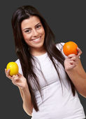 Young pretty girl holding orange and lemon over black background — Stock Photo