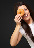 Portrait of young woman looking through a donut over black — Stock Photo