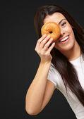 Portret van een jonge vrouw op zoek via een donut over zwart — Stockfoto